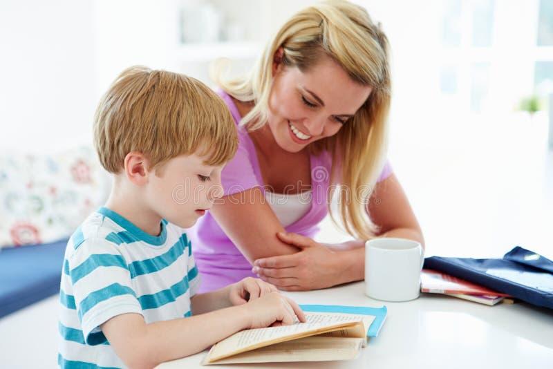 Moeder die Zoon met Thuiswerk in Keuken helpen stock foto's