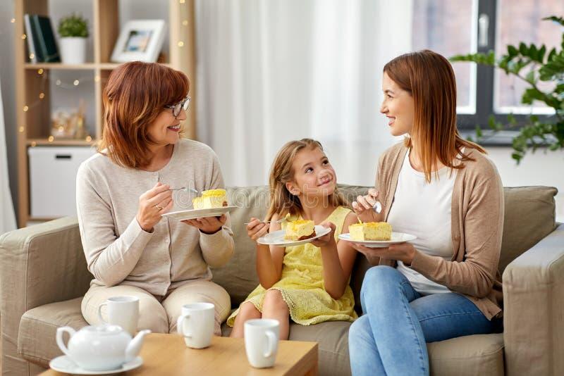 Moeder, dochter en grootmoeder die cake eten stock fotografie