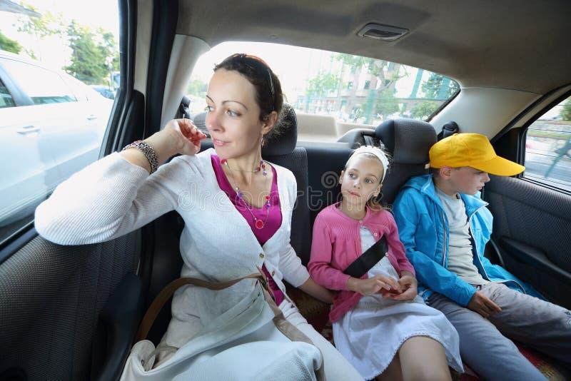 Moeder, dochter en zoon in auto stock foto