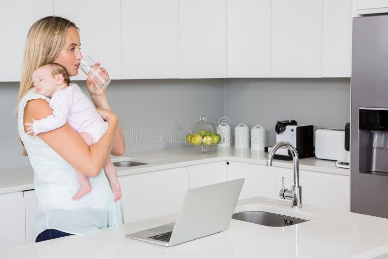 Moeder drinkwater terwijl het vervoeren van baby in keuken stock afbeelding