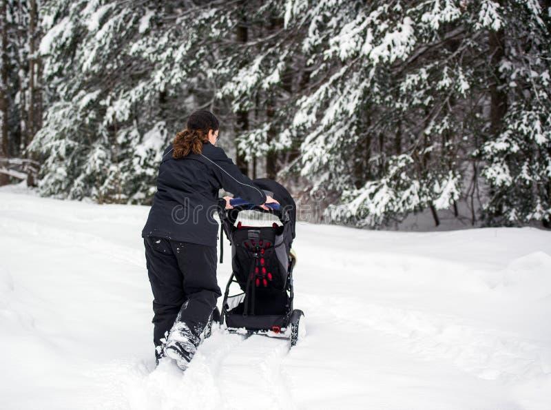 Moeder Duwende Wandelwagen in Diepe Sneeuw royalty-vrije stock afbeelding