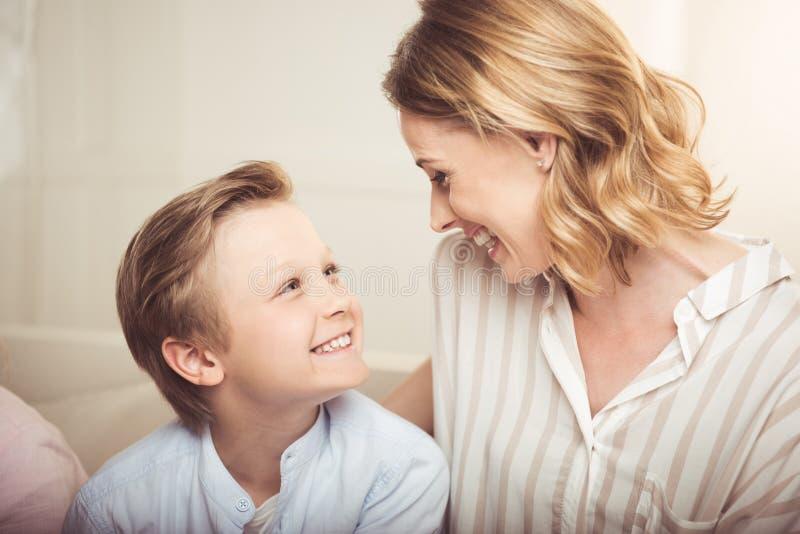 Moeder en aanbiddelijk weinig zoon die elkaar thuis glimlachen royalty-vrije stock afbeeldingen
