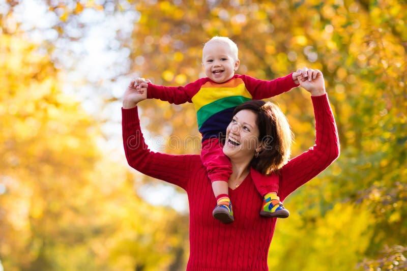 Moeder en baby in de herfst Pret van de dalings de openluchtfamilie stock afbeeldingen