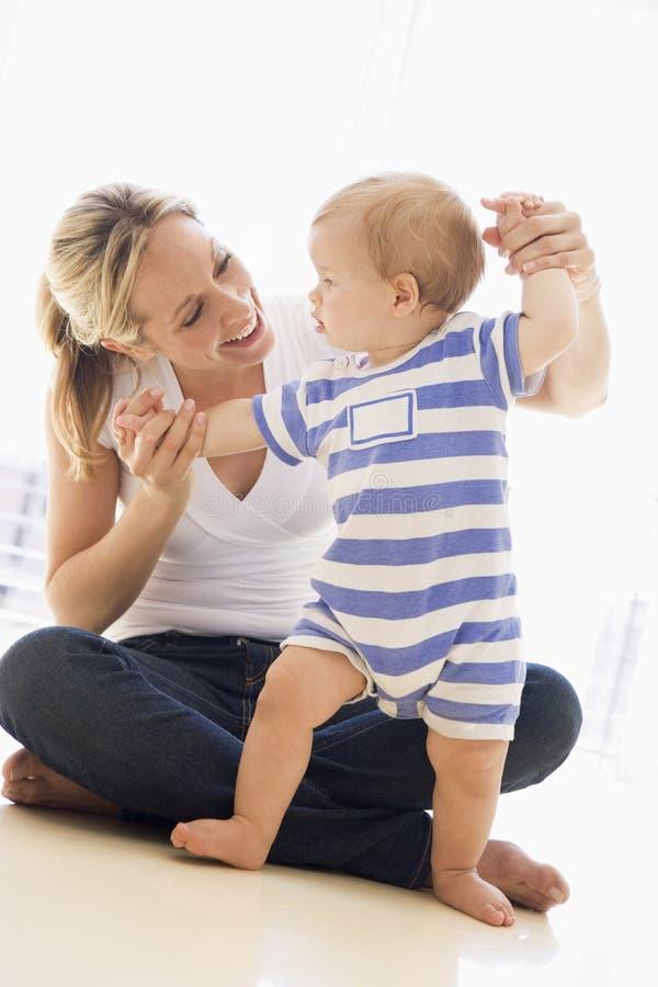 Moeder en baby die binnen spelen stock foto's