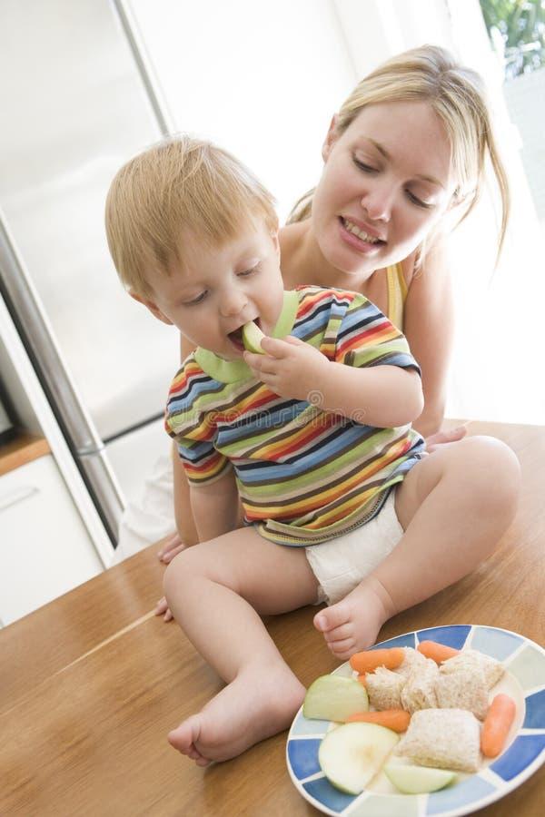 Moeder en baby die fruit en groenten eten royalty-vrije stock afbeelding