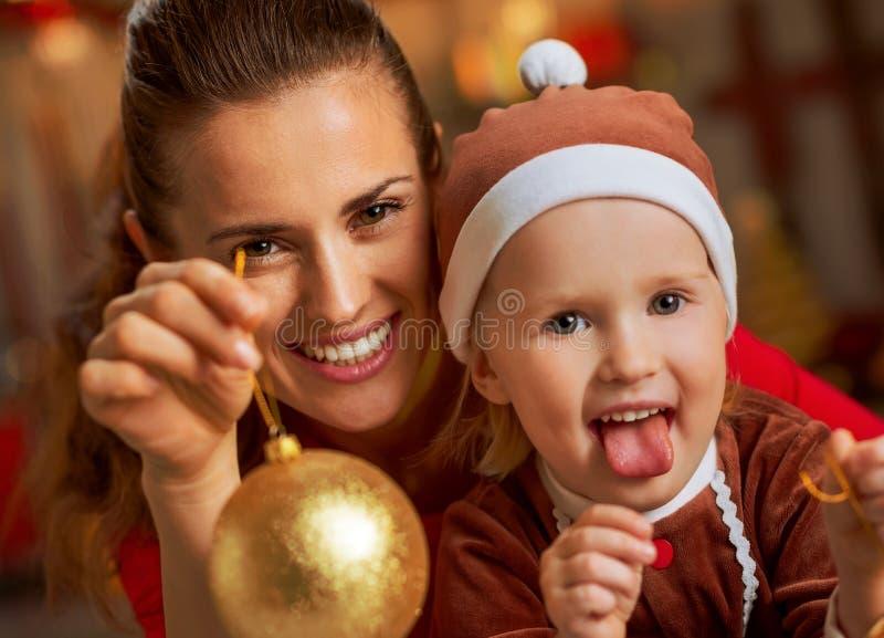 Moeder en baby die Kerstmisbal tonen stock afbeelding