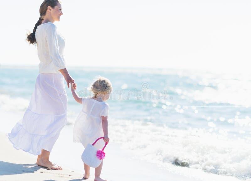 Moeder en baby die op zee kijken stock afbeeldingen