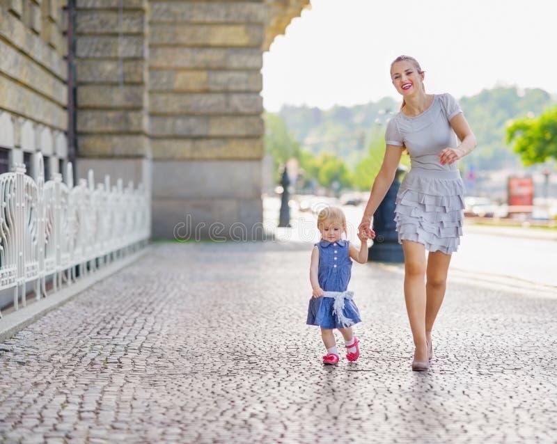 Moeder en baby die in stad lopen stock afbeeldingen