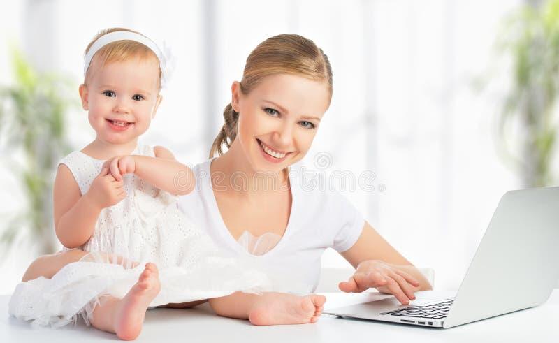 Moeder en baby die thuis laptop computer met behulp van royalty-vrije stock afbeelding