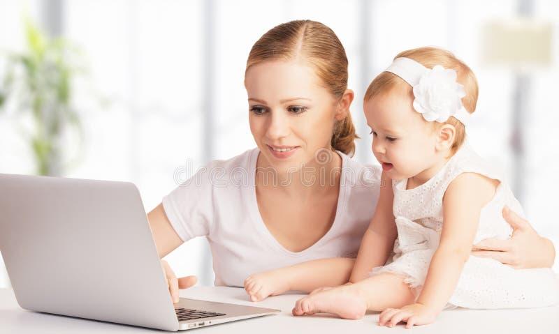 Moeder en baby die thuis laptop computer met behulp van royalty-vrije stock fotografie