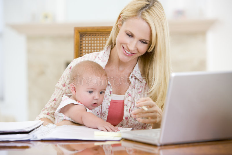 Moeder en baby in eetkamer met laptop royalty-vrije stock afbeeldingen