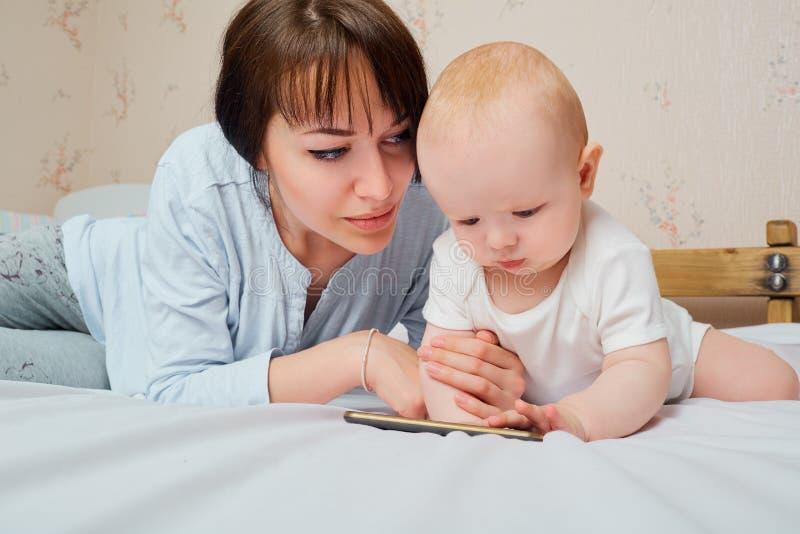 Moeder en baby het spelen met telefoon op het bed De moeder kijkt royalty-vrije stock afbeelding
