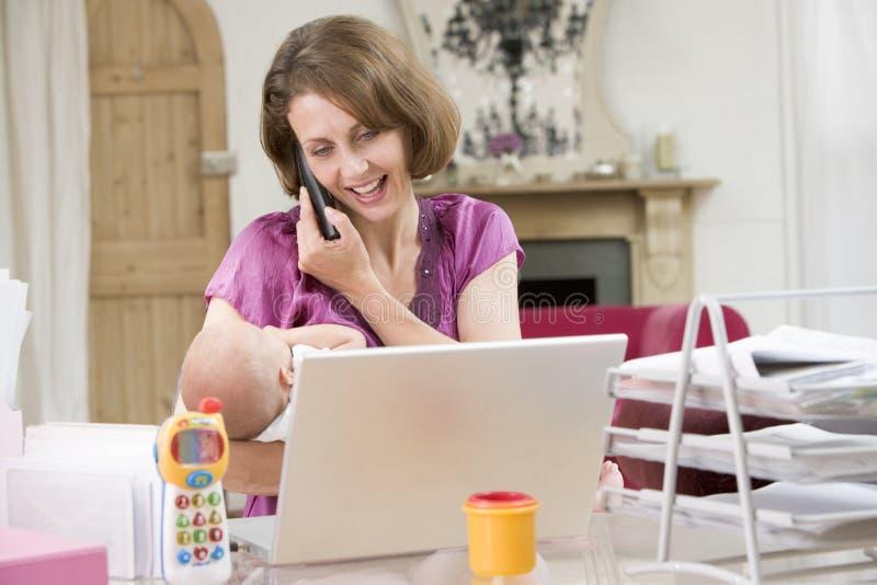 Moeder en baby in huisbureau met laptop royalty-vrije stock afbeeldingen