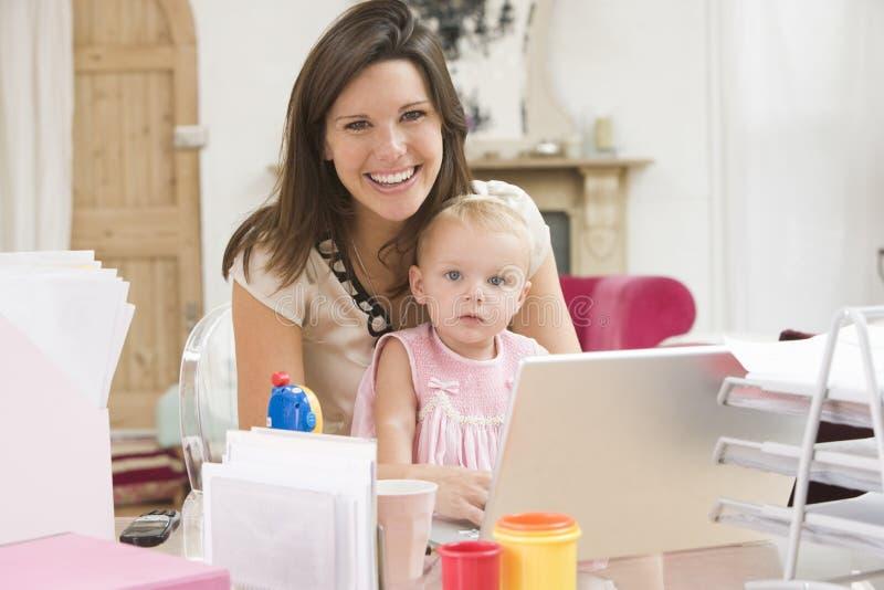 Moeder en baby in huisbureau met laptop stock afbeeldingen