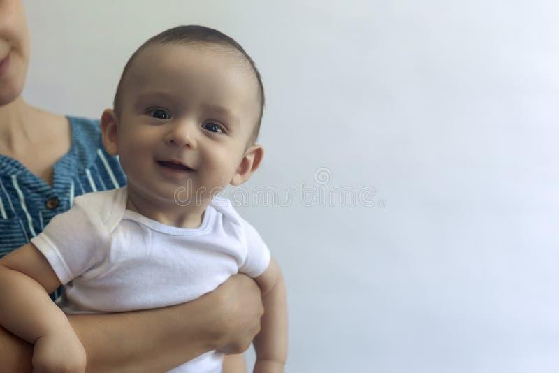 Moeder en Baby Mamma dat haar jongen van de 6 maandenbaby houdt Mooie babyjongen van zes maanden in de handen van zijn moeder Jon royalty-vrije stock afbeeldingen