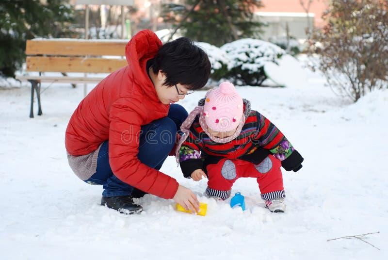 Moeder en baby om in de sneeuw te spelen stock afbeeldingen