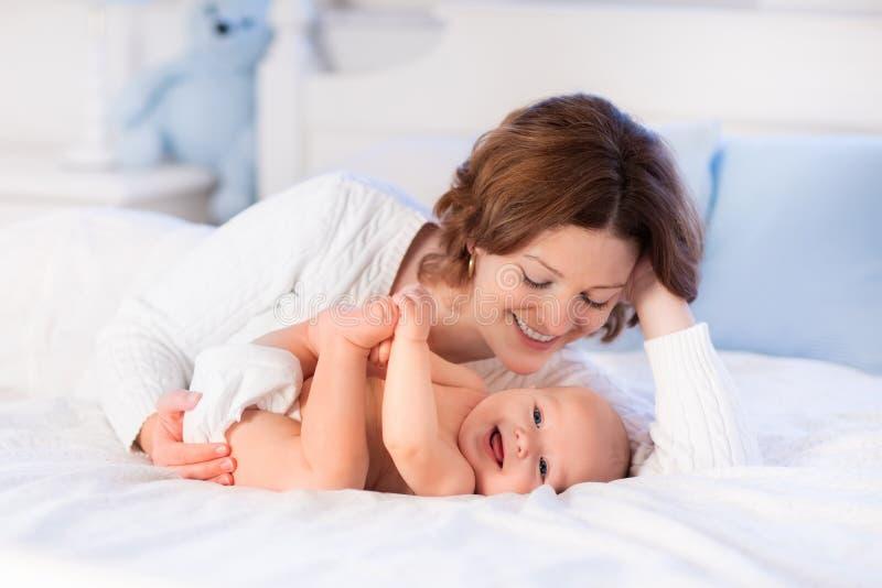 Moeder en baby op een wit bed stock foto's