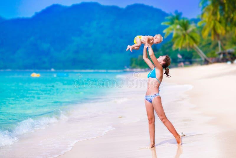 Moeder en baby op tropisch strand stock afbeeldingen