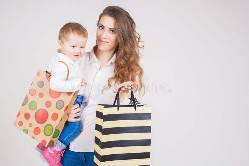Moeder en babyholdingszakken met aankopen en speelgoed royalty-vrije stock afbeeldingen