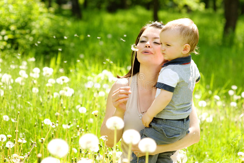 Moeder en babyjongen die op een paardebloem blazen stock foto