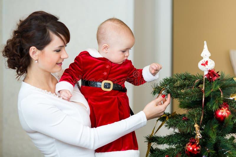Moeder en babymeisje die Kerstboom verfraaien royalty-vrije stock foto's