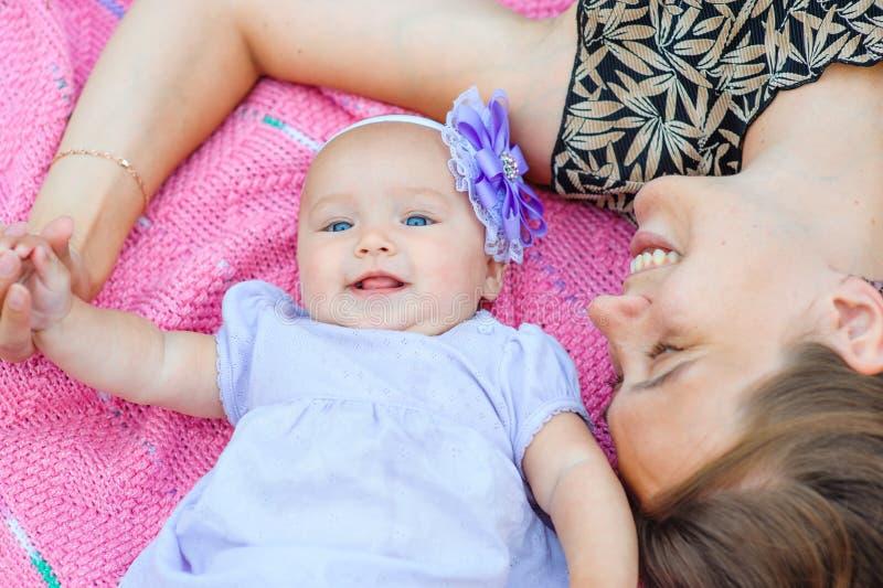 Moeder en babymeisje die op roze deken in het de zomerpark liggen royalty-vrije stock foto's