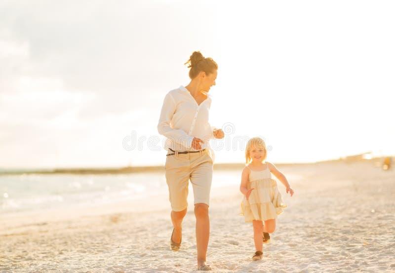Moeder en babymeisje die op strand lopen stock foto