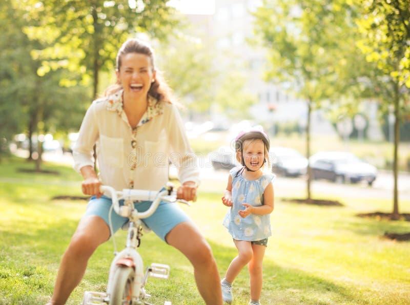 Moeder en babymeisje die pret met fiets hebben royalty-vrije stock afbeeldingen