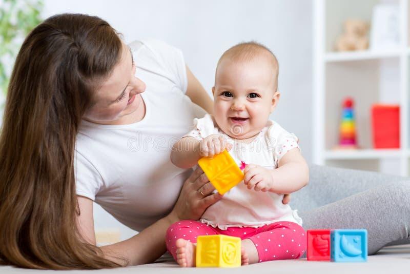 Moeder en babymeisje het spelen met kleuren ontwikkelingsspeelgoed in kinderdagverblijf royalty-vrije stock foto's