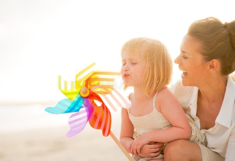 Moeder en babymeisje het spelen met windmolenstuk speelgoed stock fotografie