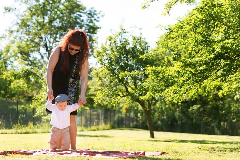 Moeder en babyspel op het gras stock foto's