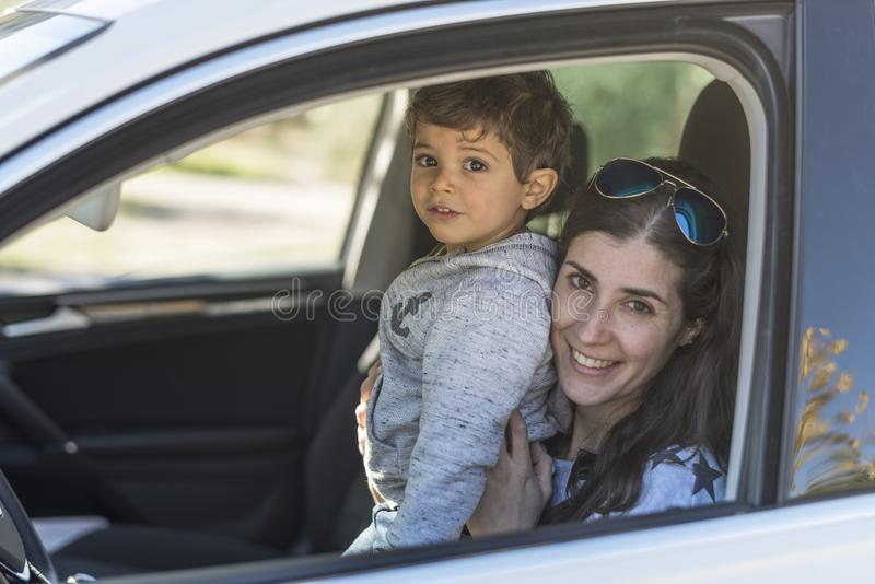 Moeder en babyzoon het stellen in portretbeeld in auto stock foto