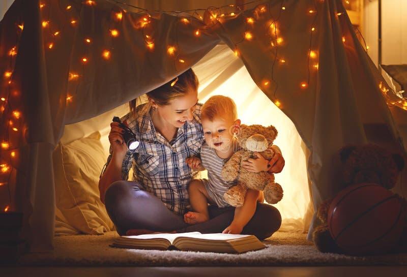 Moeder en babyzoon met een boek en een flitslicht alvorens te gaan aan stock afbeelding