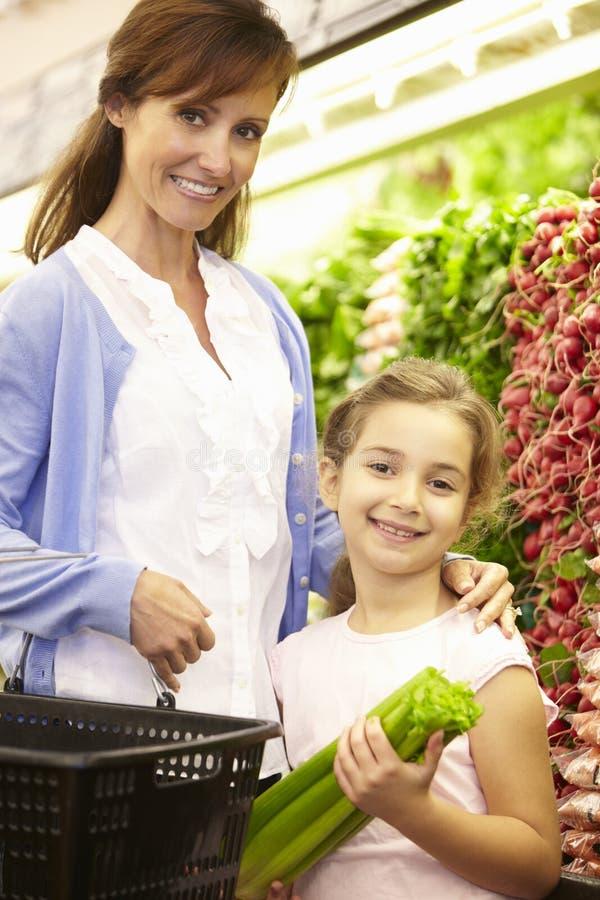 Moeder en Daughteer die voor Opbrengst in Supermarkt winkelen stock foto