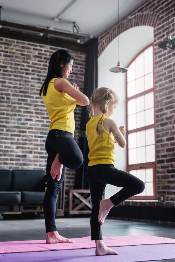 Moeder en de dochter die de sporten dragen die het praktizeren yoga kleden die samen status op één been mediteren met dienen gebe royalty-vrije stock foto
