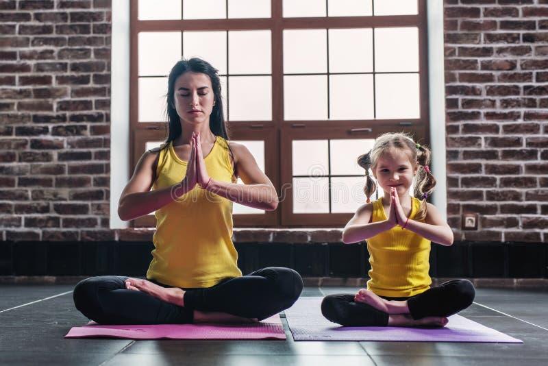 Moeder en de dochter die terwijl het doen van yoga oefenen thuis het zitten in Padmasana-het ontspannen op mat uit de glimlachen stock foto