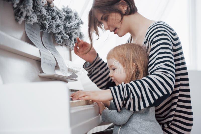 Moeder en de dochter die witte piano de spelen, sluiten omhoog wiew royalty-vrije stock foto