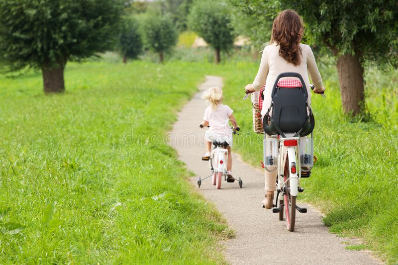 Moeder en dochter berijdende fietsen in park stock afbeeldingen