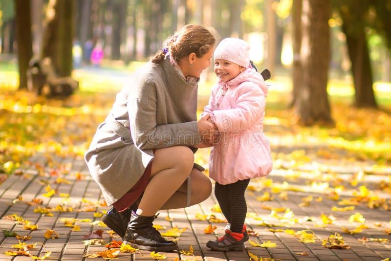Moeder en dochter in de herfstpark Familielevensstijl De gelukkige moeder en het kind brengen samen tijd in openlucht door stock fotografie