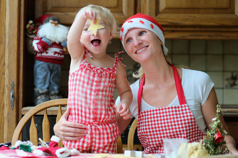 Moeder en dochter de koekjes van bakselkerstmis stock afbeeldingen