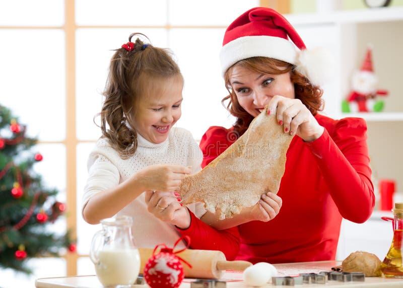 Moeder en dochter de koekjes van bakselkerstmis bij verfraaide boom Het mamma en het kind bakken Kerstmissnoepjes Familie met jon stock foto