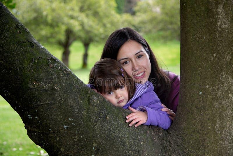 Moeder en Dochter die aangezien zij op een Boom rusten knuffelen royalty-vrije stock foto