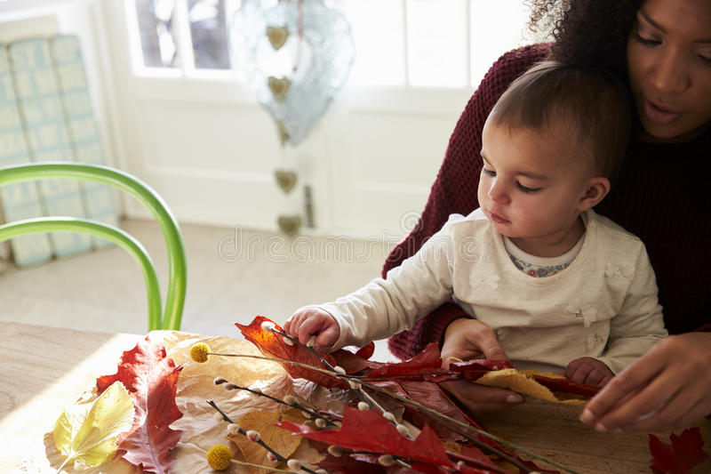 Moeder en Dochter die Autumn Decoration At Home maken stock foto