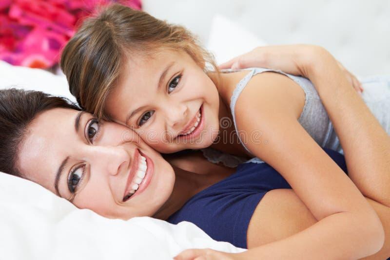 Moeder en Dochter die in Bed samen liggen royalty-vrije stock afbeelding