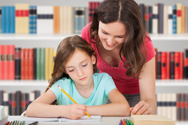Moeder en dochter die in bibliotheek bestuderen royalty-vrije stock afbeeldingen
