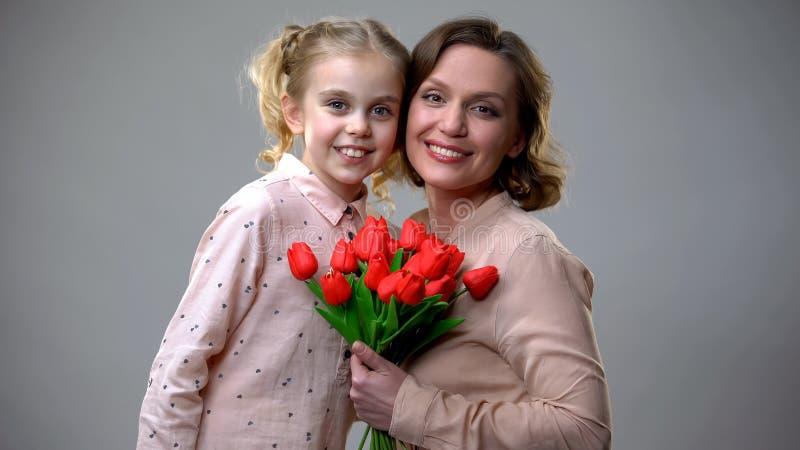 Moeder en dochter die en camera koesteren bekijken, die bloemen houden, mums dag stock foto