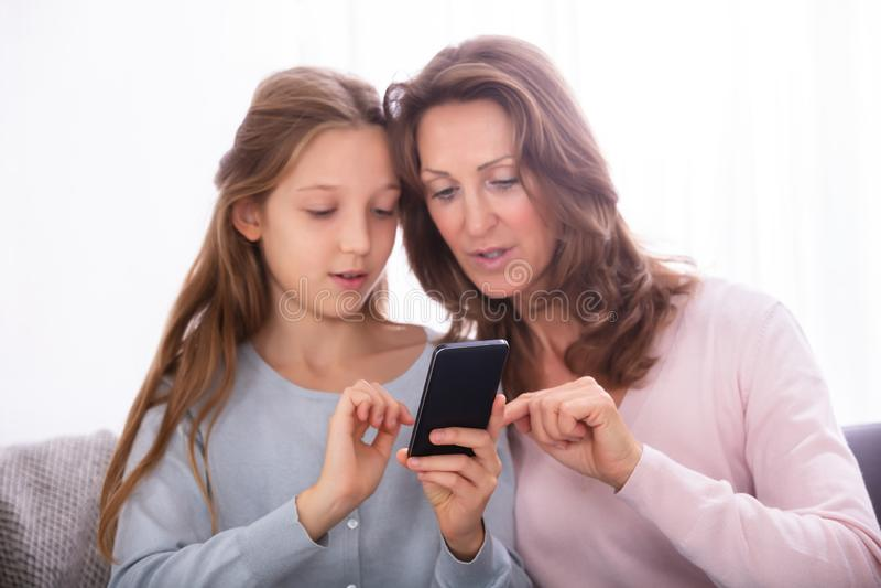 Moeder en Dochter die Cellphone gebruiken stock afbeeldingen