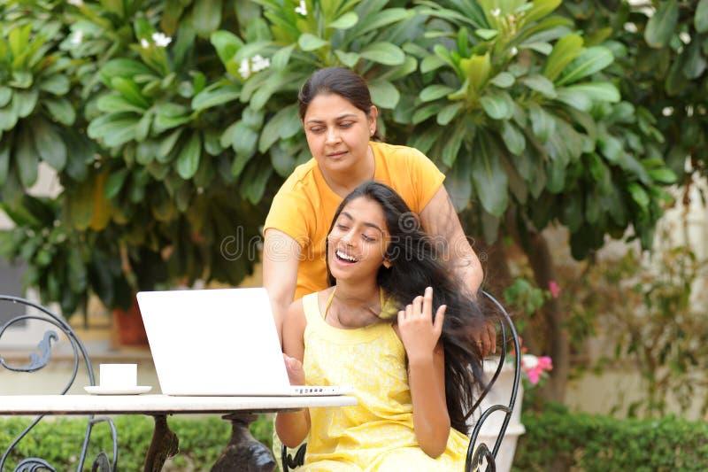 Moeder en dochter die computer in openlucht delen stock afbeeldingen