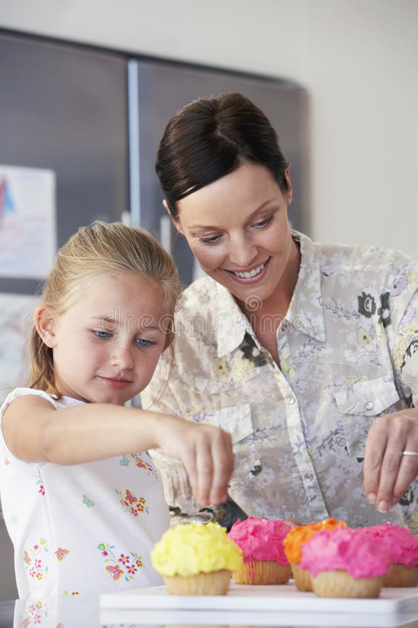 Moeder en Dochter die Cupcakes verfraaien stock foto's