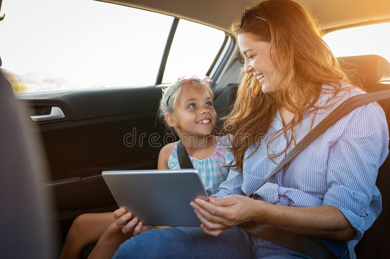Moeder en dochter die digitale tablet in auto gebruiken stock afbeeldingen